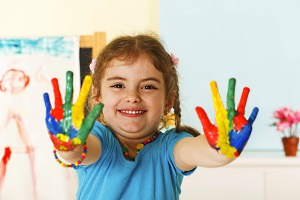 Smiling child holding up colorful painted palms
